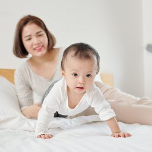 Mother looking at crawling baby